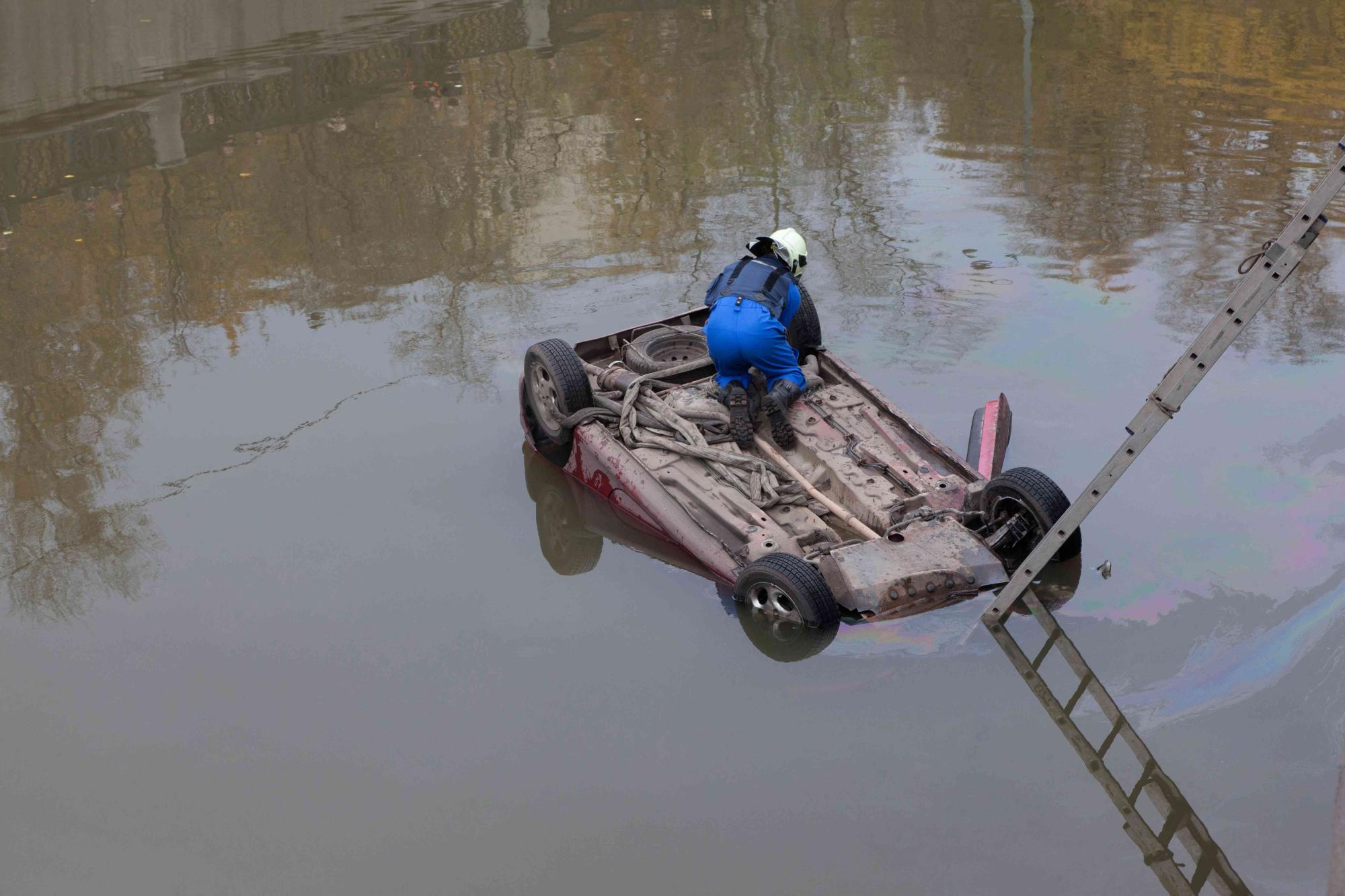 car fell into water and capsized. Rescuer attaches the rope.